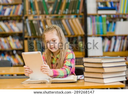 Teen girl with tablet computer working in library