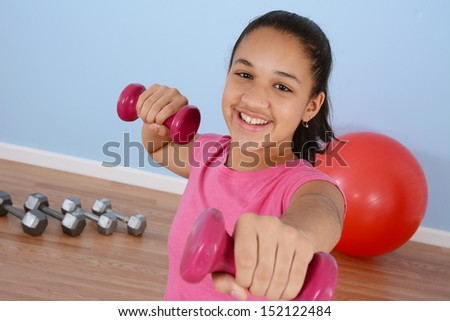 Teen girl working out in the gym - stock photo