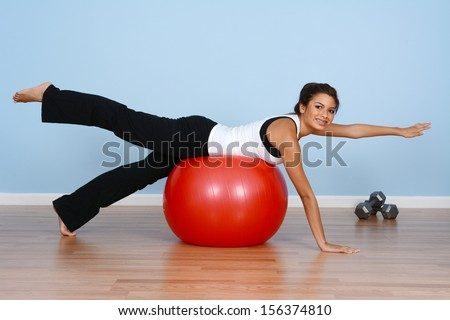 Teen girl working out while at the gym - stock photo