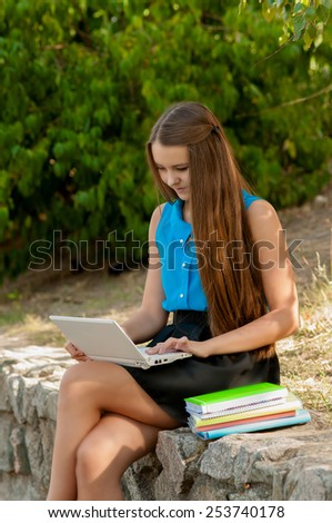 Teen girl works with the laptop in headphones and books sitting on the curb - stock photo