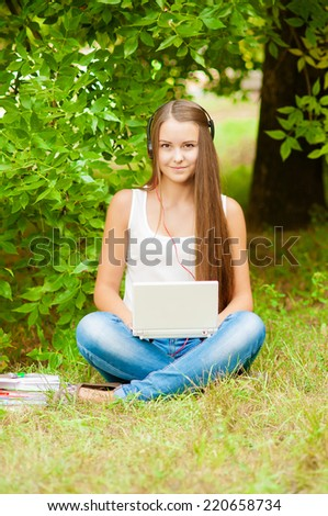 Teen girl works with the laptop on the grass near the tree - stock photo