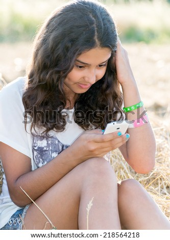 Teen girl writes a sms in  field