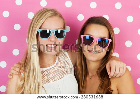 Teen girlfriends with sunglasses for pink background - stock photo