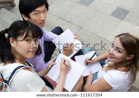 Teen girls and boy writing in books. American and Asian students study outside of school campus. Friends working together on homework - stock photo