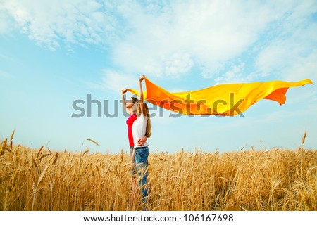 Teen girls at a wheat field with yellow fabric - stock photo