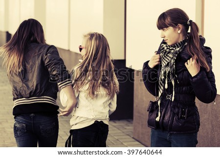 Teen girls in conflict on city street - stock photo