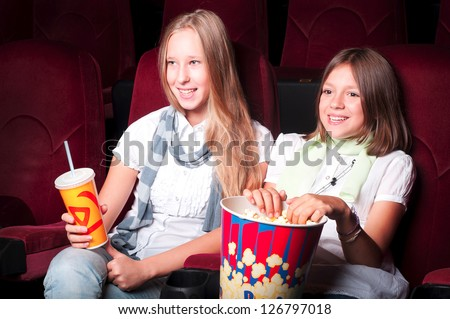 teen girls in the movie theater, holding popcorn and a drink and look at the screen - stock photo