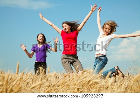 Teen girls jumping at a wheat field in a sunny day