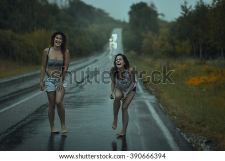 Teen girls laughing on the road in the rain - stock photo