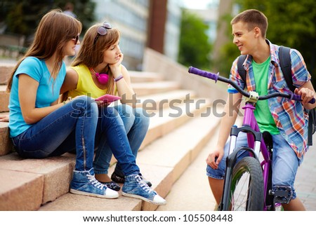 Teen girls seeming to be interested in the guy riding the bike - stock photo