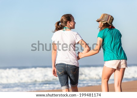 Teen Girls Talk Fun Time Beach Waves Teen girls walking together social talk fun laugh time hanging out at beach with ocean waves. - stock photo
