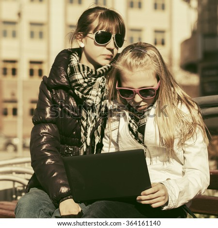 Teen girls using laptop on the bench - stock photo
