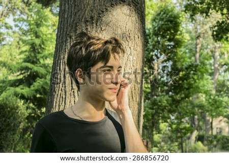 teen guy near the tree with the phone - stock photo