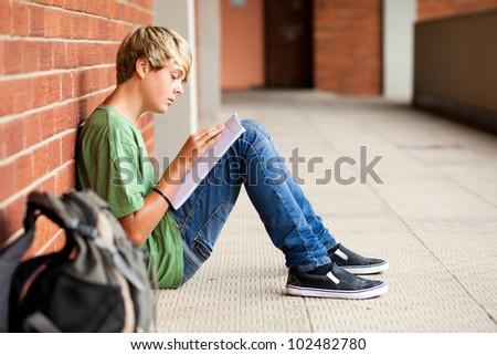teen high school student reading book in school passage - stock photo