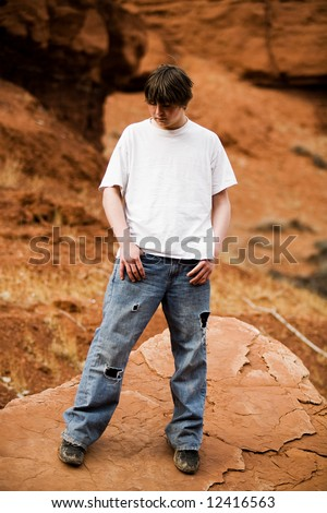 Teen in nature, in wilderness area standing on large flat rock