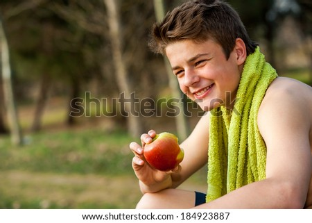 Teen jogger eating apple after exercise outdoors.