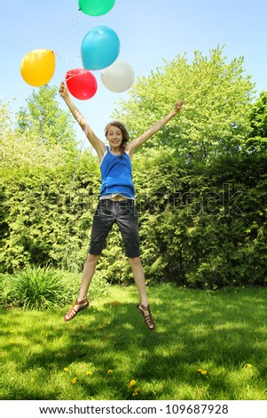 Teen jumping on grass holding a bunch of balloons