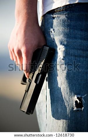 Teen male holding modern 9mm handgun, limited depth of field closeup - stock photo