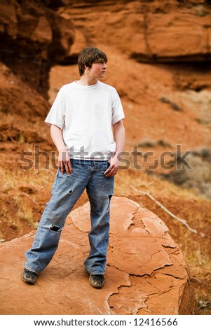 teen male in nature wilderness area, standing on a rock with holes in jeans, hands in pockets.