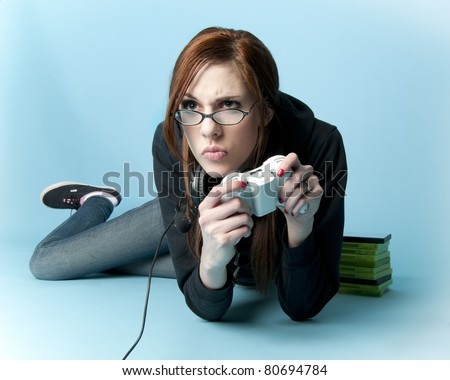 Teen model holding video game controller lying on floor - stock photo