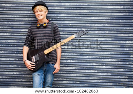 teen musician portrait with guitar outdoors - stock photo