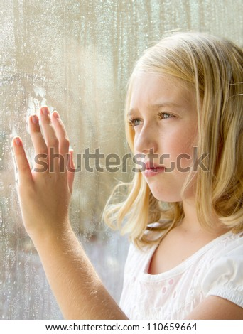 Teen or child looking out a window with rain - stock photo