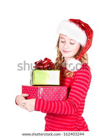 Teen or child wearing Santa hat holding Christmas presents on an isolated white background  - stock photo