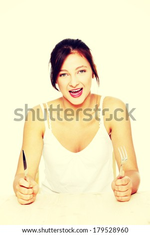 Teen pretty caucasian screaming girl sitting behind the table with fork and knife. Isolated on white.