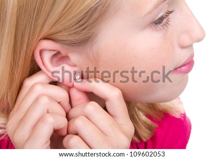teen putting in earring isolated on white