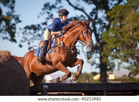 Teen rider leaps across a platform on a cross country course - stock photo