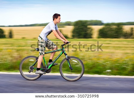 Teen riding a bike on country road - stock photo