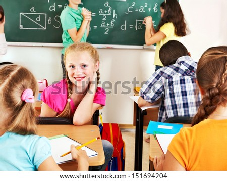 Teen school child sitting on desk in classroom.