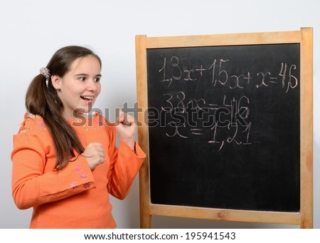 Teen schoolgirl near a school board rejoices correctly solving the equation
