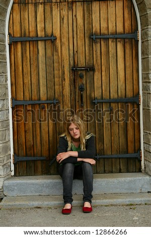 Teen  sitting on church steps. - stock photo