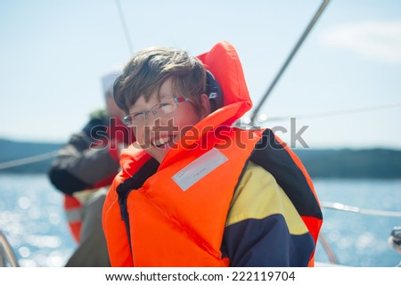 Teen smiling while wearing a life jacket with sea in the background. - stock photo