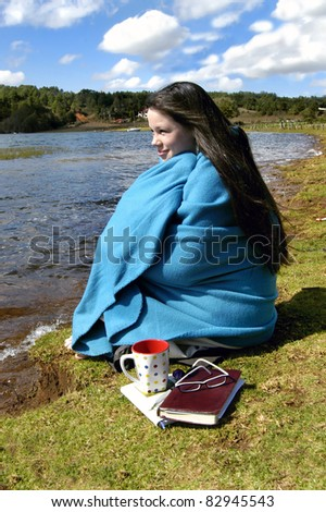 "Teen spends some ""alone time"" at lake side resort in Mexico.  She is wrapped in a blanket and drinking a cup of coffee.  Her Bible and journal lays besides her."