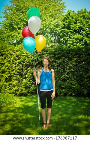 Teen standing on grass holding a bunch of balloons