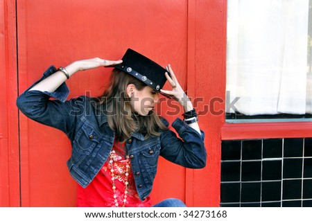Teen strikes a theatrical pose while wearing a western and spanish style black leather hat.  She is in profile and unsmiling. - stock photo