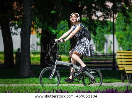 Teen student girl or young woman in plaid dress rides a folding bicycle and listens music in white earphones in the park. Summer healthy leisure in town - stock photo