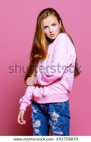 Teen style. Beautiful young model with long hair posing at studio in jeans and pink sweatshirt. Beauty, fashion.