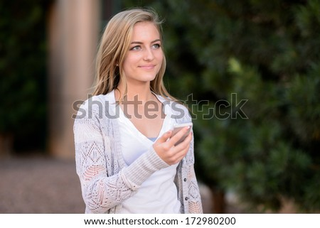 Teen using a cellphone. Woman using a cellphone outside a building with a green tree in the background. - stock photo