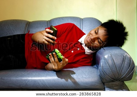 Teen using a smartphone while lying down on a couch and smiling Photo of a Teen using a smartphone while lying down on a couch and smiling