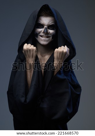 Teen with make-up of the skull in a black cloak showing his fists