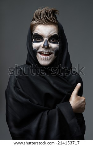 Teen with makeup skull cape showing thumbs up