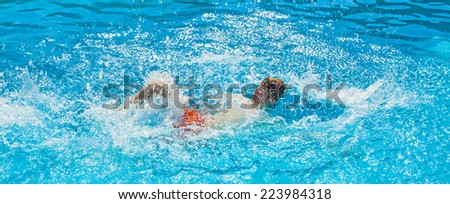 teen with red shorts dives in the pool - stock photo