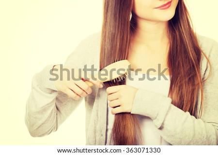 Teen woman brushing her hair. - stock photo