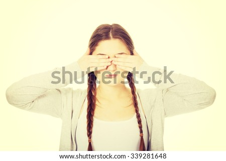 Teen woman covering her eyes with both hands. - stock photo