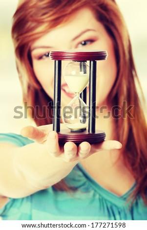 Teen woman holding hourglass - stock photo