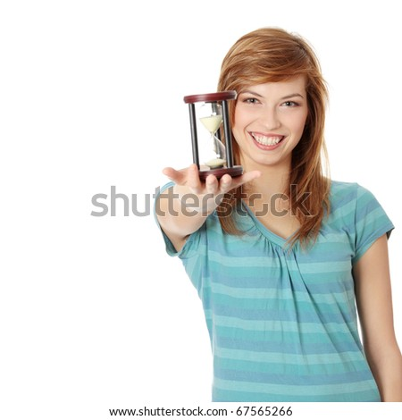 Teen woman holding hourglass, isolated on white - stock photo