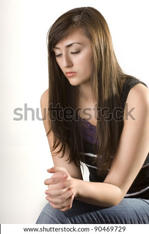 Teen woman praying over Bible on knees with hands folded - stock photo
